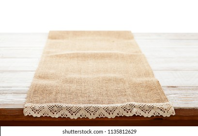 Empty canvas napkin with lace, tablecloth on wooden table on white background. Can used for display or montage your products. Selective focus