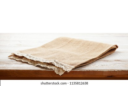Empty canvas napkin with lace, tablecloth on wooden table on white background. Can used for display or montage your products. Selective fokus