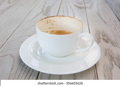 empty cappuccino cup on wood surface