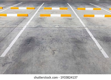 An empty car park and white lines outside the building