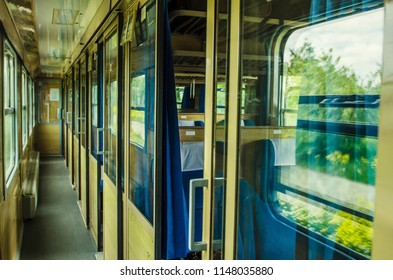 empty car of the train of the long-distance message. Inside of old public railway train cabin with seats, handrails, fan and interior in vintage style service for passenger transport