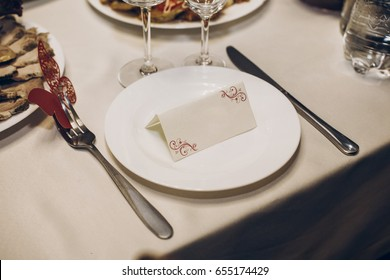 empty card on plate on table with cutlery, setting at wedding reception in restaurant, luxury catering. menu or guest invitation