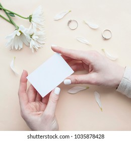 Empty card with rings and flowers.  Top view composition with girl's hand holding card. Flat lay business card. Mockup template. View from above.