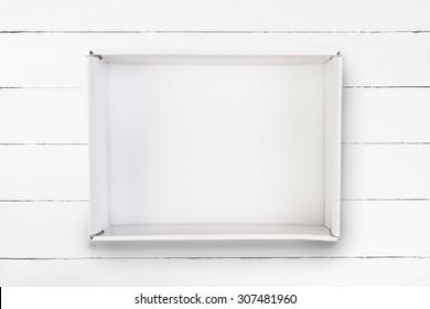 Empty cardboard box on white wooden background