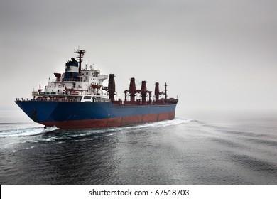 The empty cargoship going through passage Dardanelless, Turkey, in rainy weather
