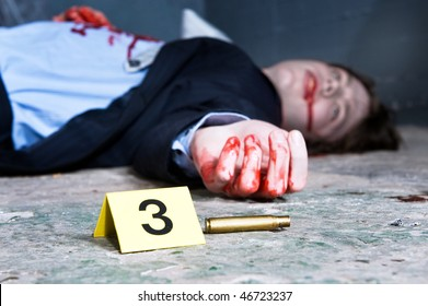 Empty cartridge found on a crime scene with a yellow placard with number three and a dead body in the background