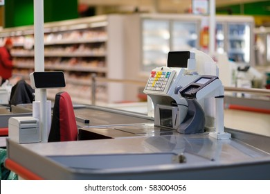 Empty cash desk with screens and card payment terminal with shelves and fridges on blurry backgrounds
