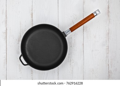 Empty cast iron frying pan on a wooden table closeup, top view