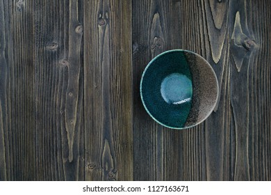 Empty ceramic bowl on wooden table background.