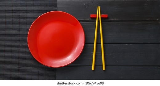 Empty ceramic dish or plate and asian chopsticks on black wooden background