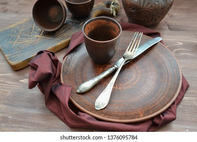 Empty ceramic dishware and wooden objets with grenadine napkin flat view