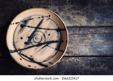 Empty ceramic plate on the wooden background with blank space