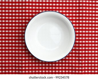 Empty cereal bowl isolated on red and white checkered background