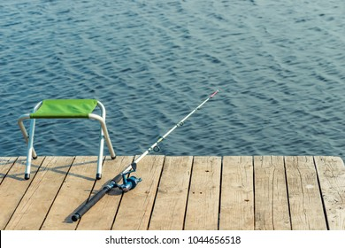 an empty chair and a fishing pole on a wooden pier near the lake