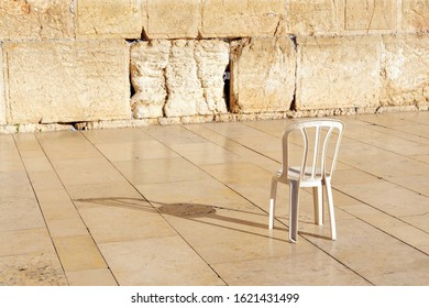 An empty chair at the Kotel Wailing Western Wall, a remnant of the ancient wall that surrounded the Jewish Temple's the most sacred site recognized by the Jewish faith outside of the Temple Mountain.