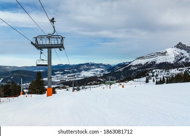 Empty chair lift at french Villard de Lans ski resort surrounded by snowy Vercors mountains.