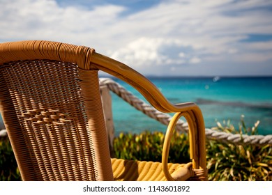 Empty chair made of rope in front of a maritime landscape and a cloudy sky.