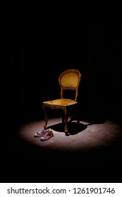 Empty chair with a pair of red sneakers under a spotlight - Girl absence suggestion - International day against women's violence
