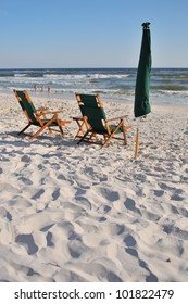 An empty chair and umbrella at the beach