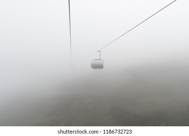 empty chairlift and cable in a bleak and foggy mountain landscape in the early autumn in a ski resort in Switzerland