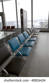 empty chairs at the airport and plane through glass