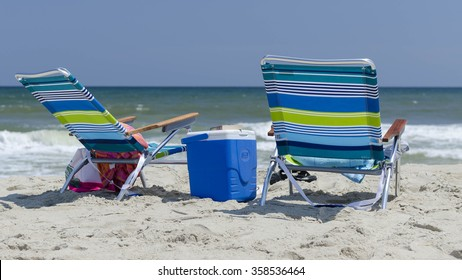 Empty chairs and cooler on beach
