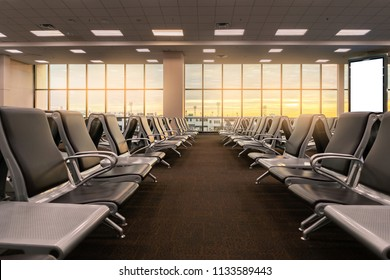 Empty chairs in the departure hall at airport , with the control tower with Sun rise or sunset and have billboards Mockup .Travel and transportation concepts.