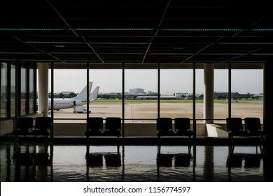 Empty chairs in the departure hall at airport with airplane background.Travel concept.