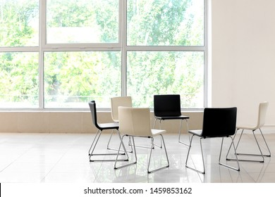 Empty chairs prepared for group therapy indoors