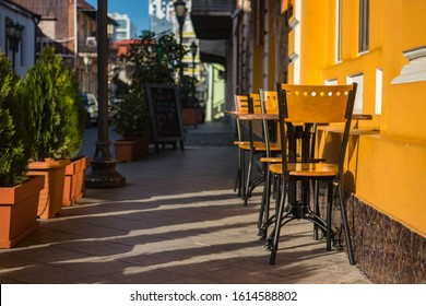 Empty chairs of summer cafe standing outside on the street in historical part of touristic European city old center, Morning light.