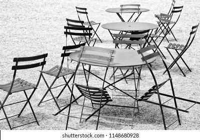 Empty chairs an tables on a terrace, black and white photo