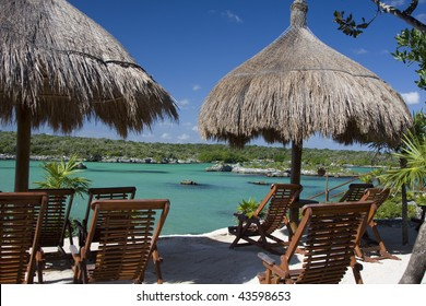 empty chairs and umbrellas along side of the lagoon at Xel-Ha in Mexico