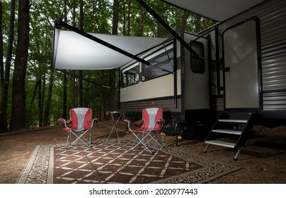 Empty chairs under the awning of a travel trailer at Jordan Lake