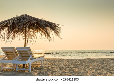empty chairs under thatched umbrellas on a sandy beach