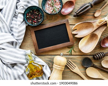 Empty chalk board and kitchen utensils with spices on a white wooden background