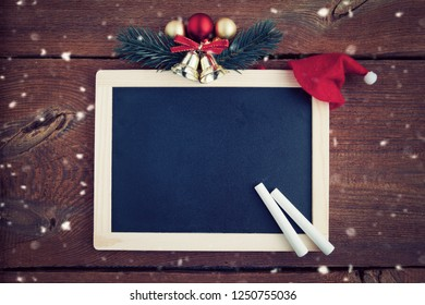 empty chalk board surrounded of christmas decoration , copy space