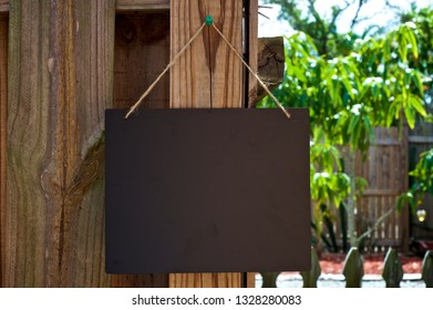 A empty chalkboard sign hanging from jute rope outdoors on old wooden fence.