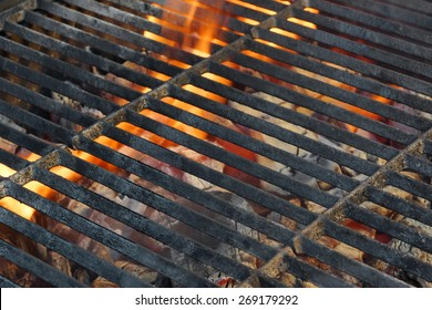 Empty Charcoal Grill With Glowing Embers and Flames Of Fire In The Background
