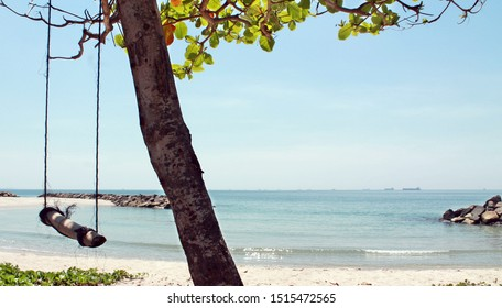Empty children swing under the tree on the seascape background