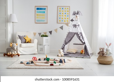 an empty children's playroom with tent and  toy railway