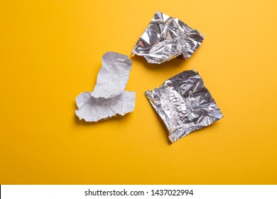 Empty chocolate candy wrappers on yellow background, plastic and paper wrappers