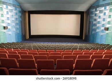 Empty cinema auditorium with line of chairs and stage with silver screen. Ready for adding your own picture.