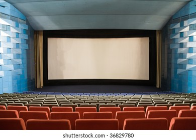 Empty cinema auditorium with line of chairs and stage with projection screen. Ready for adding your own picture.