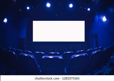 Empty cinema auditorium with empty white screen. Empty rows of theater or movie seats. Blue toned.