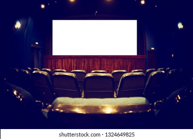 Empty cinema auditorium with empty white screen. Empty rows of theater or movie seats. Toned.