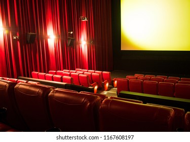 Empty cinema with blank screen and rows of red seats