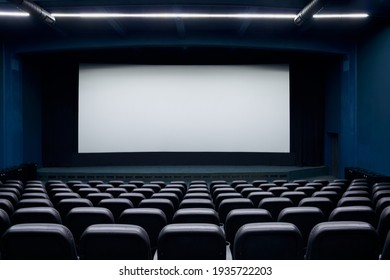 Empty cinema hall with screen and black row chairs. Concept of empty modern movie theatre.