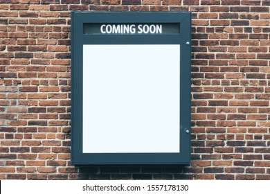 Empty cinema poster panel on brick wall of theater walkway