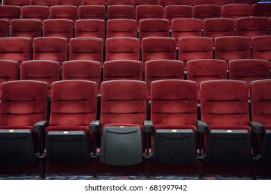 Empty cinema room with red chairs