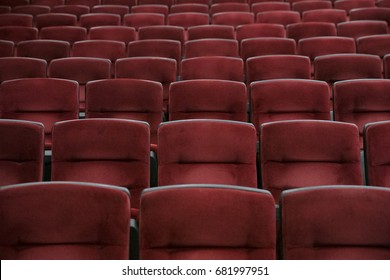 Empty cinema room with red chairs closeup
